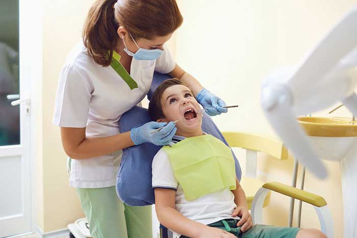 kids dentist gives an exam to a young boy